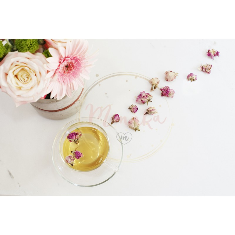 A cup of healthy herbal tea with dried roses  Beautiful fresh flowers on  light marble table, top view  Pink roses and gerberas on a female work  desk