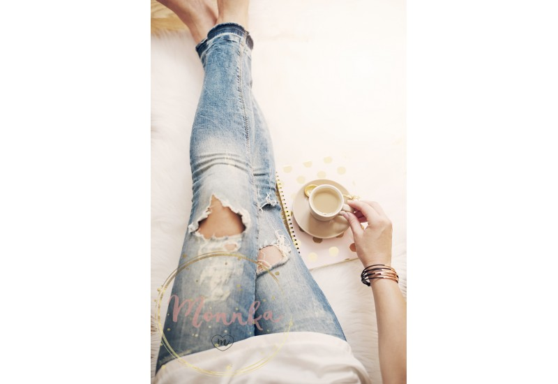 A young woman wearing distressed jeans sitting on wood floor on a white fur carpet at home and holds a cup of coffee in his hand. Gold bright feminine theme - DIGITAL DOWNLOAD PHOTOGRAPHY
